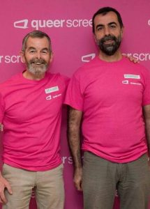 Two Queer Screen volunteers in pink t-shirts stand side by side smiling
