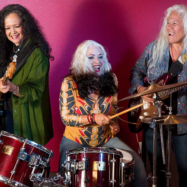 Three Filipina-American woman in their 60s stand in front of a red wall, the one on the left holds a bass, the one at the middle is sitting at a drum kit, and the other on the right is playing a guitar
